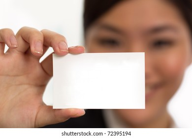 A woman holding a card with her face out of focus