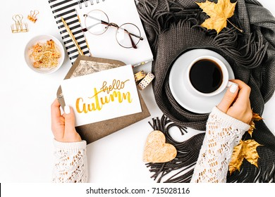 Woman holding card with word Hello Autumn. Workspace with laptop,  coffee cup wrapped in scarf,   glasses. Stylish office desk. Autumn  concept.  Flat lay, top view
