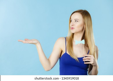 Woman holding carnival accessoies on stick having fun. Studio shot on blue background.