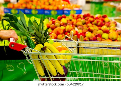 Woman holding cart with fresh fruits and vegetables in shopping centre. Healthy eating concept. Closeup.