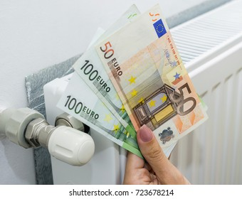 Woman holding cash in front of heating radiator. Payment for heating in winter. Selective focus.