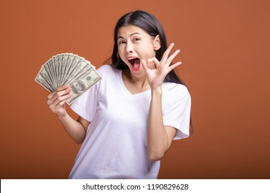 Woman holding cash notes isolated in orange background. Young asian woman in white t-shirt in big winning pose, Okay sign. Young rich hipster concept.