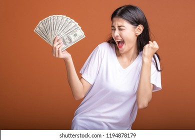 Woman holding cash notes isolated in orange background. Young asian woman in white t-shirt in winning pose, holding dollar note. Young rich hipster concept.