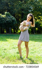 Woman holding a cat in a park outdoors