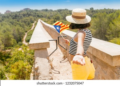 Woman holding Catalan flag outdoors