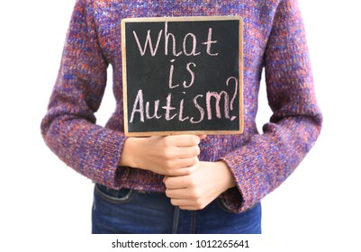 "Woman holding chalkboard with phrase ""What is autism?"" on light background"
