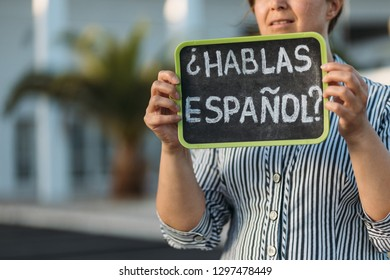 Woman holding a chalkboard with the question habla espanol? Do you speak spanish? Written in spanish is it