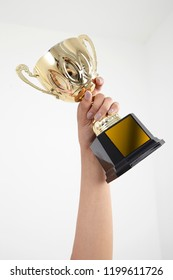 Woman holding a champion gold trophy isolated on white background