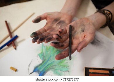 Woman holding charcoal pencil at table