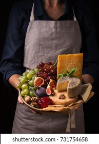 Woman holding a cheese plate with fruits and jam