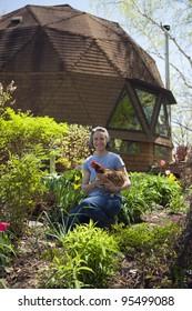Woman holding chicken in her garden