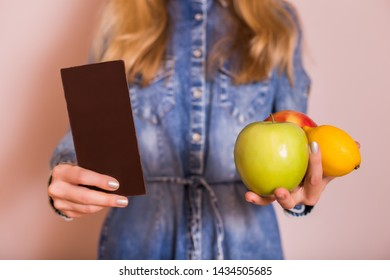 Woman holding chocolate and fruit.It is time for diet and healthy eating concept.
