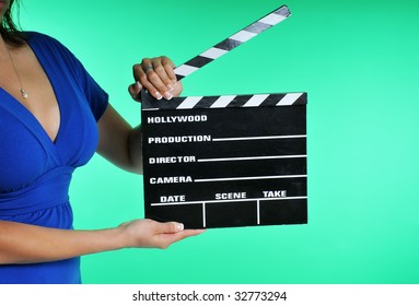 woman holding a clapper board on a green screen