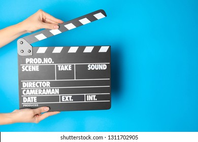 Woman holding clapperboard on color background, closeup with space for text. Cinema production