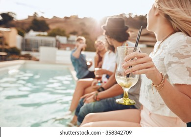 Woman holding a cocktail glass while sitting on the edge of swimming pool with friends. Young people enjoying a poolside party with drinks. Focus on hand and cocktail glass.