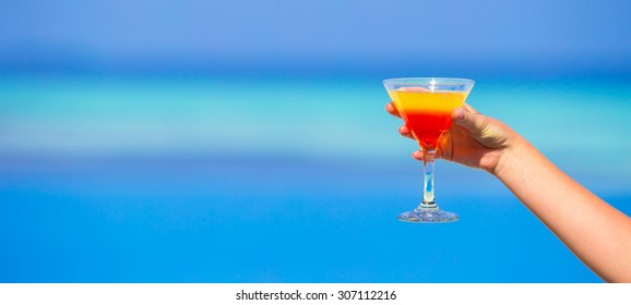Woman holding cocktail on tropical beach