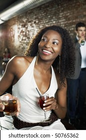 Woman holding cocktail, sitting in bar