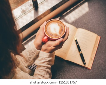 Woman holding a coffee cup and looking at the window in rainy day.