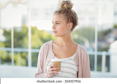 Woman holding coffee cup while standing at office