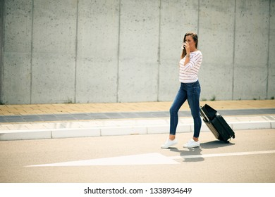 Woman holding coffee and luggage while walking on the street.