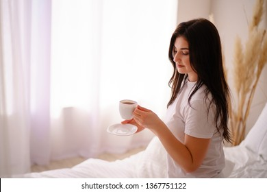 Woman holding a coffee mug at home. Young smiling girl enjoy morning coffee in bed. Daily routine, starting new day, good mood and harmony