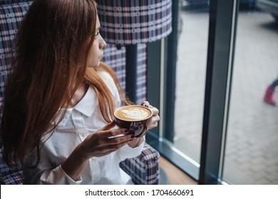 Woman holding coffee mug looking in the window
