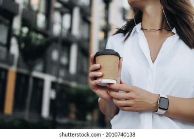 Woman holding coffee in paper cup