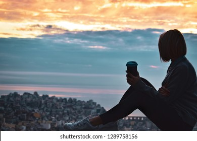 Woman holding coffee tumbler cup while sitting outdoor and enjoying sunrise with cityscape at background. Space for text
