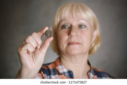 Woman holding coin on grey background. Selective focus on coin.