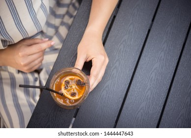 Woman holding a cold summer cocktail with coffee beans and orange slice. lifestyle people concept. space for text. top view