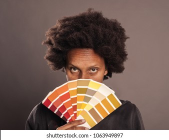 woman holding a color palette on a gray background