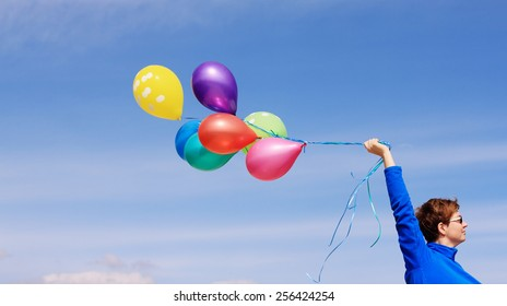 woman holding colorful balloons outside