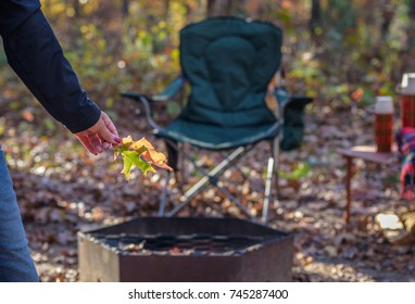 woman holding colorful fall leaves in sunlight at campsite