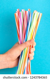 Woman is holding colorful plastic straws in hand on bright background. Event and party supplies. Earth pollution concept
