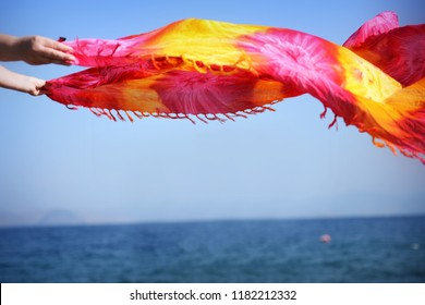 Woman holding colorful scarf by the sea