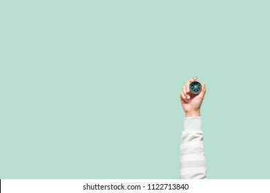 Woman holding compass in one hand on green background, searching direction with compass.
