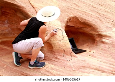 A woman holding a computer mouse while peering at her laptop computer around a rocky corner.