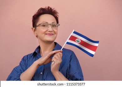 Woman holding Costa Rica flag. Nice portrait of middle aged lady 40 50 years old with a national Costa Rican flag over wall background. Visit Costa Rica concept.
