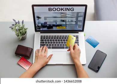 woman holding credit card and computer with app hotel booking screen