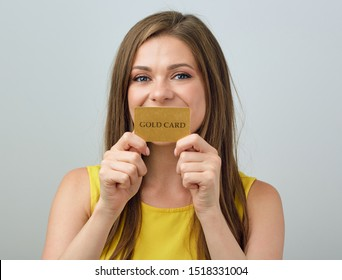 Woman holding credit card in front of mouth. Isolated female face portrait.