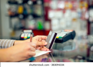 Woman holding credit card in hand, signing slip, in the store