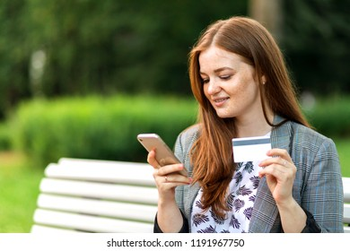Woman holding credit card and using mobile smartphone outdoor, online shopping