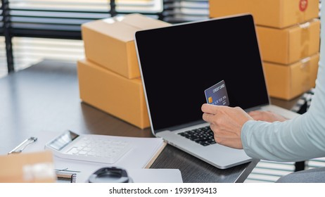 A woman holding a credit card and using a laptop Online Payments, Online Shopping Ideas and SME Online Selling