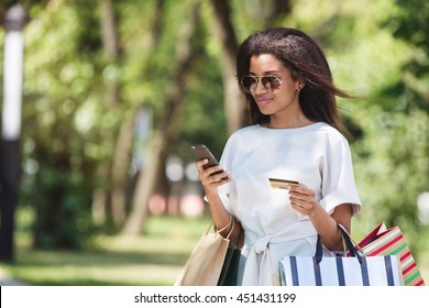 Woman holding a credit card and using cell phone for online shopping