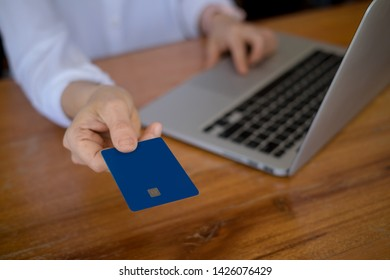 woman holding credit card while working on project while sitting at office with laptop. Achievement business career concept.