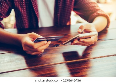 Woman holding credit cards and mobile phones are now shopping over the internet by paying by credit card.