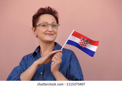 Woman holding Croatia flag. Nice portrait of middle aged lady 40 50 years old with a national Croatian flag over pink wall background.Learning Croatian language. Visit Croatia concept.