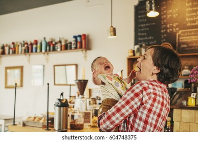 A woman holding a crying baby in a coffee shop