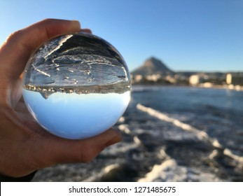 Woman holding a crystal ball, looking through the ball to the coastline and Montgo mountain in Javea / Xabia on the Costa Blanca, Spain. Creative photography, crystal ball refraction.