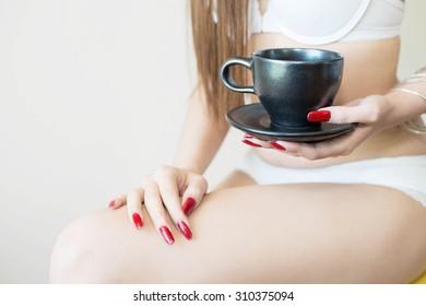 Woman holding a cup and a bikini.